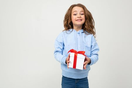 girl dressed in pink clothes holds a gift box with a red ribbon on a white background with copy space.