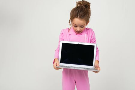 Closeup portrait of attractive funny charming baby in pink costume showing laptop screen with mock up on white background.