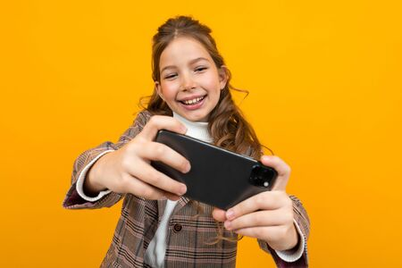 laughing stylish blonde girl in a classic jacket plays games on a smartphone on a yellow studio background. Zdjęcie Seryjne - 139903044