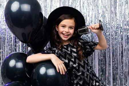 portrait of a young brunette singer in a black dress singing with a microphone in her hands on a shiny background in helium balloons.