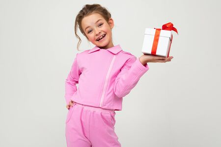joyful happy Caucasian girl in a pink suit holds a box with a gift with a red ribbon for a birthday on a white background.