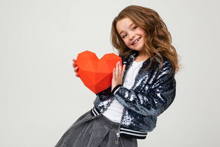 stylish girl holding a paper heart for Valentines Day on a white background.