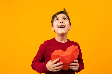funny cheerful handsome caucasian boy with paper heart for valentines day on orange background. Zdjęcie Seryjne - 139903049