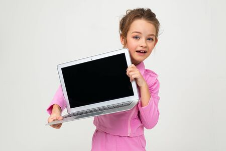 Closeup portrait of an attractive young girl in a pink suit showing a laptop screen with a mockup on a white background. Zdjęcie Seryjne - 139903051
