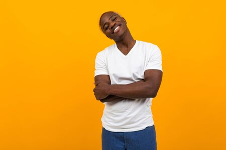 attractive african guy in a white t-shirt on a yellow background with copy space.