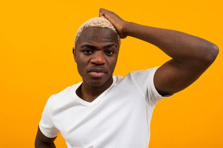 young black african man in white t-shirt thinking on yellow isolated background with copy space. Zdjęcie Seryjne - 139903054