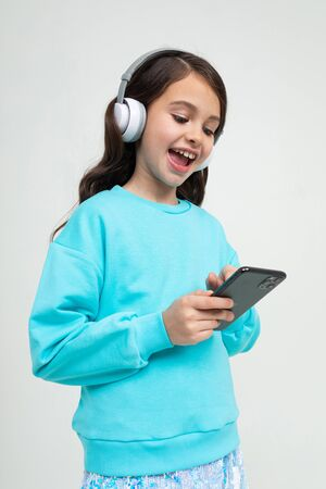 girl in a blue blouse relaxes with music in large stylish headphones.