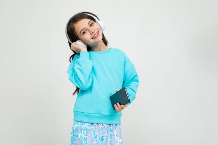 young girl in a turquoise blouse listens to music with headphones holding a phone on an isolated studio background with copy space. Zdjęcie Seryjne - 139903056