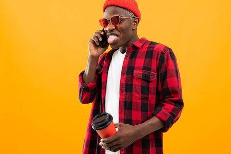 Portrait of a black american handsome stylish man wearing a checkered red shirt holding a drink glass on a coffee break and talking on the phone on a yellow background with copy space. Zdjęcie Seryjne
