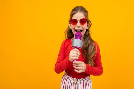 cute european girl singing into a microphone on a yellow background. Zdjęcie Seryjne - 139903060