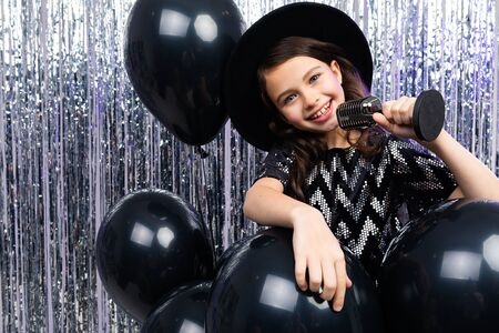 portrait of a young brunette singer in a black dress singing with a microphone in her hands on a shiny background in helium balloons. Zdjęcie Seryjne - 139903063