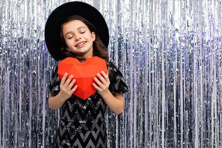 Smiling cute girl in a festive dress and hat holds a red paper heart on a shiny background with tinsel. Valentines Day. Zdjęcie Seryjne - 139903061