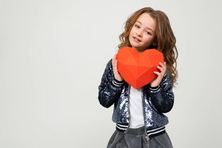 closeup portrait of a smiling stylish caucasian girl holding a red paper heart for valentines day on a white background with copy space. Zdjęcie Seryjne - 139903062