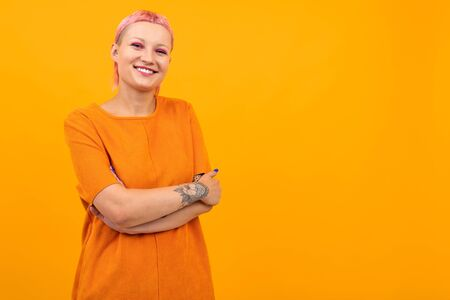 Extraordinary beautiful woman with short pink hair and big tattoo on her hand smiles isolated on orange background Zdjęcie Seryjne - 139903064