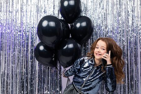 young funny caucasian girl with helium black balloons talking on the phone on a shiny tinsel background. black Friday.