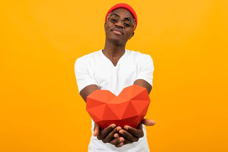 Cute handsome American in a white T-shirt holds out a red 3D heart made of paper for Valentines Day on a yellow background with copy space. Zdjęcie Seryjne - 139903067