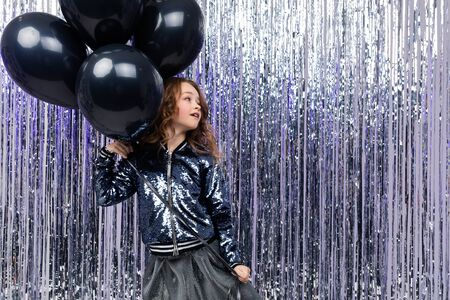 Attractive young girl holds with airy black helium balloons on a brilliant festive background. birthday party.