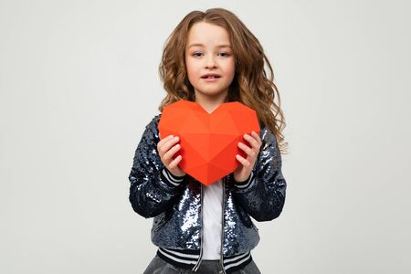 stylish girl holding a paper heart for Valentines Day on a white background with copy space. Zdjęcie Seryjne - 139903068