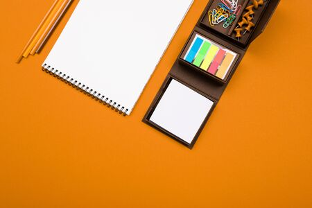 blank notebook with stationery on an orange background with copy space. office workplace.