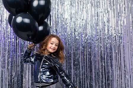 Attractive young girl holds with airy black helium balloons on a brilliant festive background. birthday party with copy space.