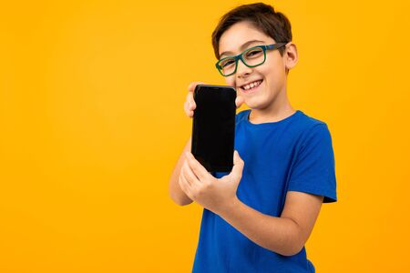 cute boy in glasses and a blue t-shirt holds the phone with the screen forward with a layout on a yellow background with copy space. Zdjęcie Seryjne - 139903070