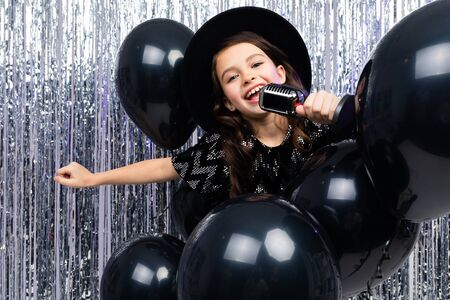 attractive european young girl singing with a microphone at a party against a background of black balloons and tinsel.