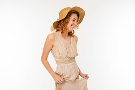portrait of a cute happy charming beautiful blond girl in a dress and a straw hat on a white background with copy space.