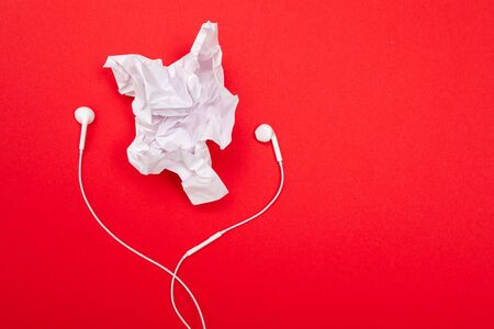 minimalism concept. crumpled sheet of paper with headphones on a red background with copy space. Reklamní fotografie