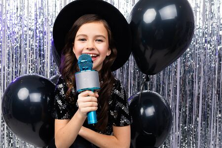 happy girl in a music song contest sings with a microphone on a shiny background with black helium balloons.