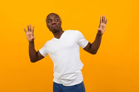 thinking african black man in a white t-shirt with a layout posing dancing on a yellow background.