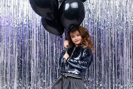 Stylish attractive girl with airy black helium balloons on a background of shiny tinsel. birthday party.