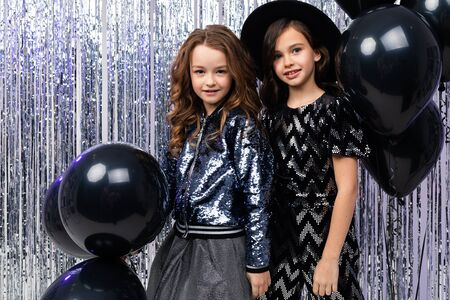 black Friday. two cute stylish young sisters in holiday dresses with black balloons on a shiny background.