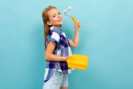 Caucasian girl paints a wall with a roller and paint isolated on blue background.