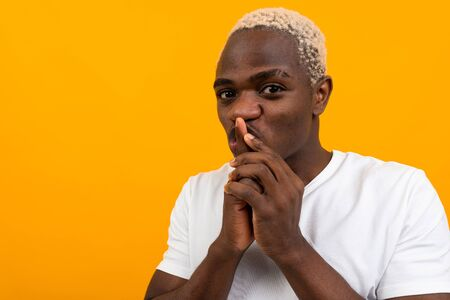 cute charming handsome black blond american man on orange background.