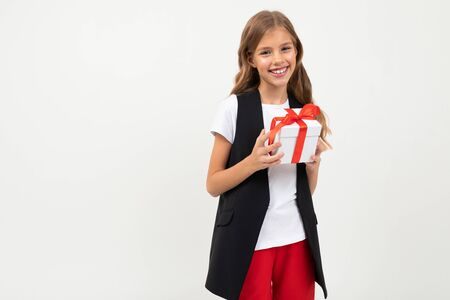 birthday concept. attractive smiling girl with a gift with a red ribbon in her hands on a white background with copy space.