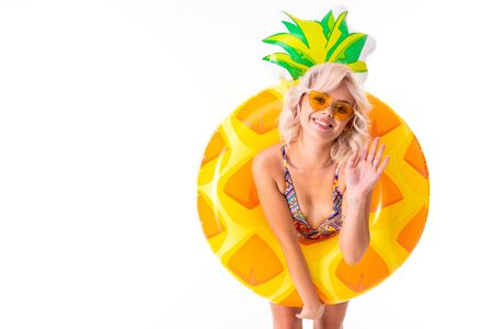 Pretty blonde caucasian female stands in swimsuit with rubber beach pineapple ring and smiles isolated on white background. Imagens