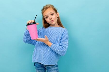 Caucasian teenager drinks coffee with pink cup isolated on blue background Imagens