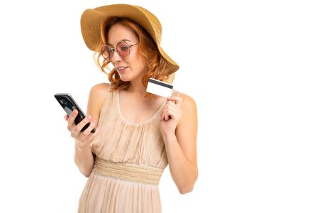 cute tourist in a hat dressed in a summer dress and sunglasses orders tickets by phone and holds a credit card with a mockup on a white background with copy space.