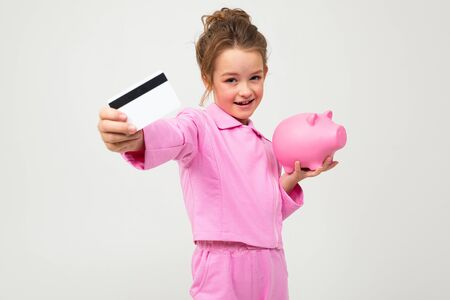 portrait of a beautiful young girl in a pink suit showing a piggy bank and a credit card with a mockup on a white background.