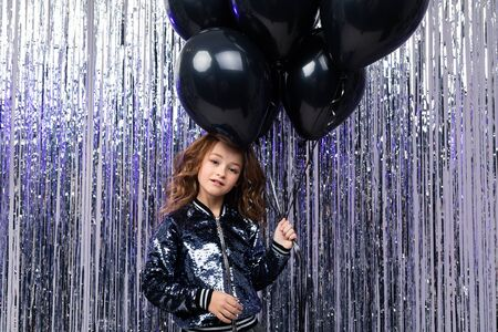 stylish girl with balloons on a background of shiny tinsel. black Friday.