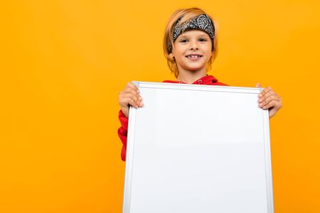 Portrait of stylish young caucasian boy with medium fair hair in red sweatshirt, black trousers and white t-shirt shows two big sheets of paper isolated on yellow background Stock fotó