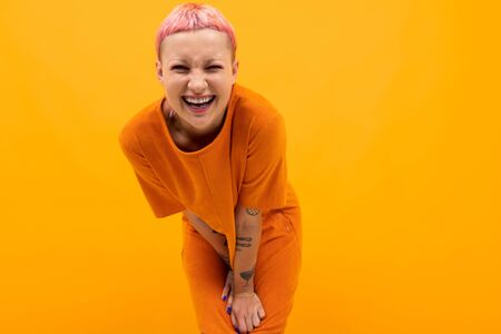 Extraordinary beautiful woman with short pink hair and big tattoo on her hand smiles isolated on orange background