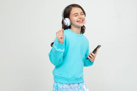young girl in a turquoise blouse enjoys music with headphones holding a phone against a studio background with copy space.