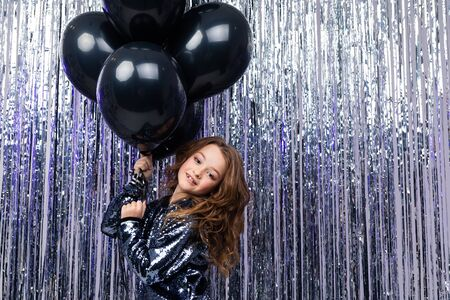 Stylish attractive girl with black balloons on a background of shiny tinsel. black Friday.