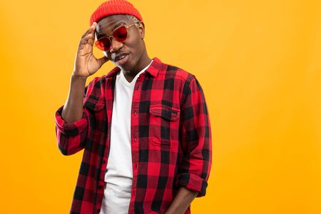 stylish serious black african guy in red retro glasses and a plaid shirt on an orange background with copy space for advertising. Imagens