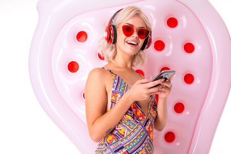 Cheerful blonde caucasian female stands in swimsuit with red sunglasses, earphones, big rubber mattress and holds a phone isolated on white background