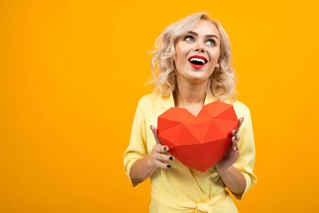 Cheerful young woman with short blonde hair smiles and holds a big red heart isolated on orange background.