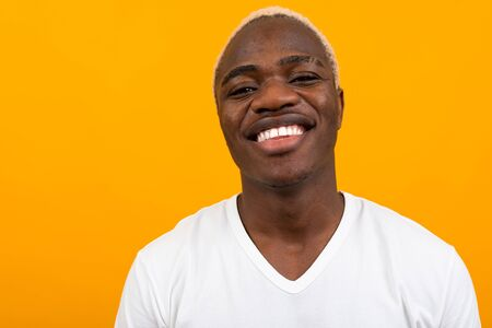 portrait of a blond smiling charismatic african black man in a white t-shirt on an orange studio background.