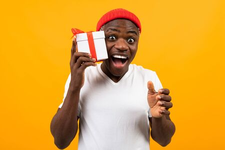 cute surprised black african man with a smile in a white t-shirt holds a box a gift with a red ribbon for a birthday on a yellow studio background. Imagens