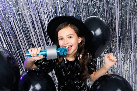 Portrait of a fashionable young girl in a black hat and a black dress singing with a microphone in her hands at a party with shiny decorations and helium balloons.